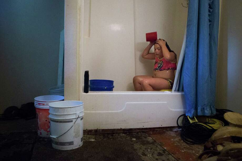Angelina Garcia, 9, bathes with rain water collected on buckets by her grandfather at their property in New King's Colony subdivision in Montgomery County, Thursday, June 30, 2016, in New Caney. Photo: Marie D. De Jesus, Houston Chronicle / © 2016 Houston Chronicle