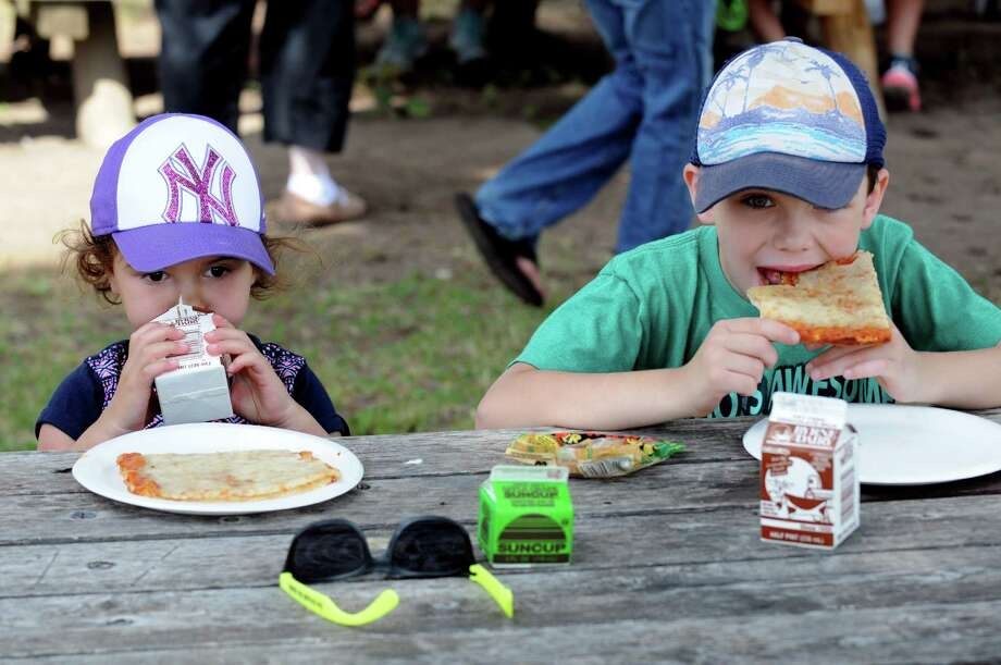 Three-year-old Clara and her brother Jacob Ziolkowski, 6, of Scotia enjoy a slice of pizza during the Schenectady Inner City Ministry free lunch program at Collins Park on Friday July 1, 2016 in Scotia, N.Y. (Michael P. Farrell/Times Union) Photo: Michael P. Farrell / 40036895A