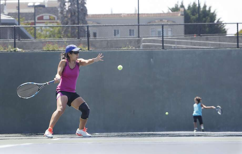 Jen Gaarder-Wang (left) plays tennis in Dolores Park while her 7-year-old daughter, Rory Gaarder-Wang, practices hitting her ball against the wall. Photo: Lea Suzuki, The Chronicle