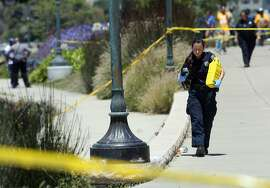 A crime scene technician carries markers as police investigate a shooting on Lakeshore Avenue in Oakland, Calif., on Friday, June 19, 2015. Three people shot five blocks from the NBA championship celebration for the Golden State Warriors in Oakland are in stable condition. Police say they received a call shortly after noon and found three male victims with gunshot wounds. (Jane Tyska/The Oakland Tribune via AP)