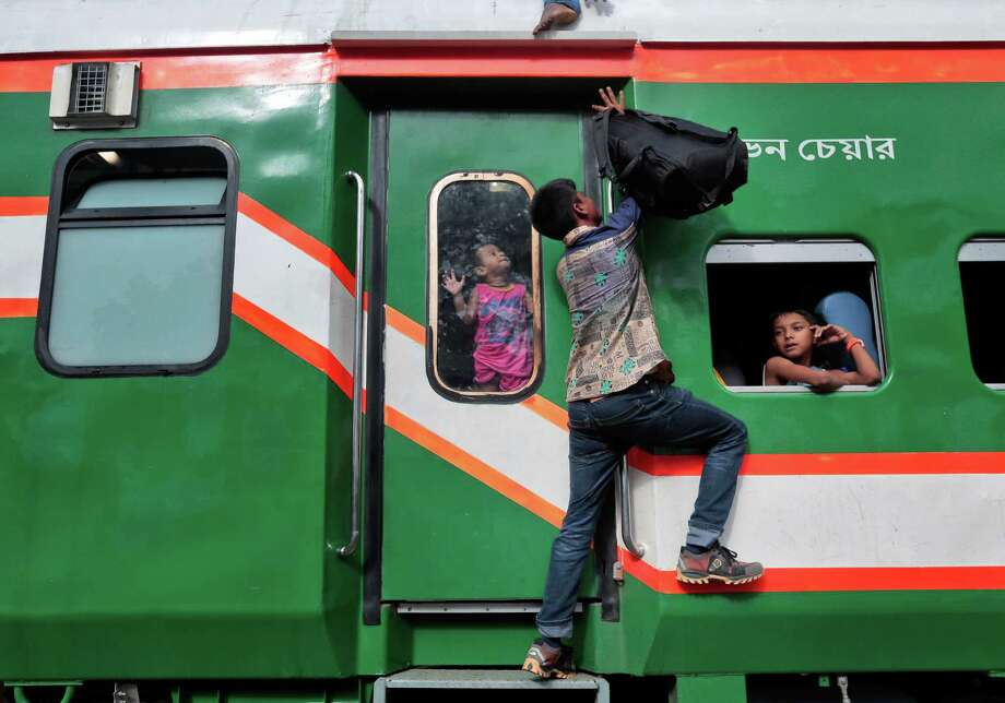 A Bangladeshi man tries to climb on the roof of an overcrowded train as he heads home ahead of Eid al-Fitr at a railway station in Dhaka, Bangladesh, Friday, July 1, 2016. Hundreds of thousands of people working in Dhaka leave for their home towns every year to celebrate Eid al-Fitr with their family. (AP Photo/A.M. Ahad) Photo: A.M. Ahad, STR / Copyright 2016 The Associated Press. All rights reserved. This material may not be published, broadcast, rewritten or redistribu