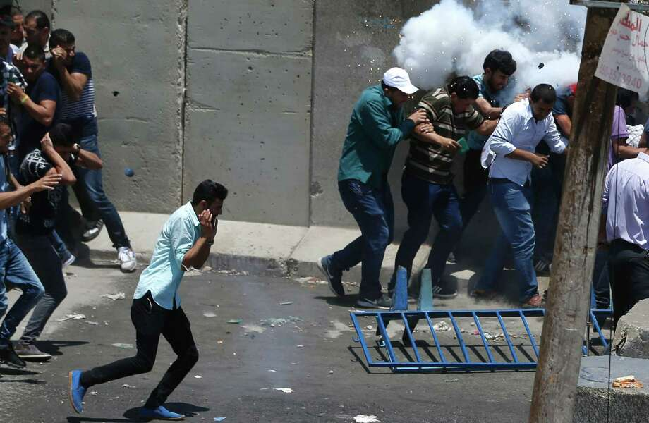 Palestinian men take cover from a stun grenade thrown by Israeli security forces during clashes at the Qalandia checkpoint Friday.  Photo: ABBAS MOMANI, Staff / AFP or licensors