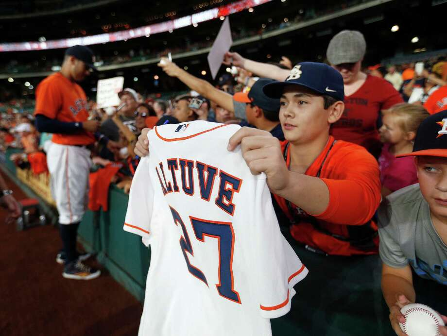 Considering the banner month Jose Altuve just had, it's safe to assume his No. 27 jersey may become a hot item for autograph-seeking fans like these Friday. Photo: Karen Warren, Staff / © 2016 Houston Chronicle