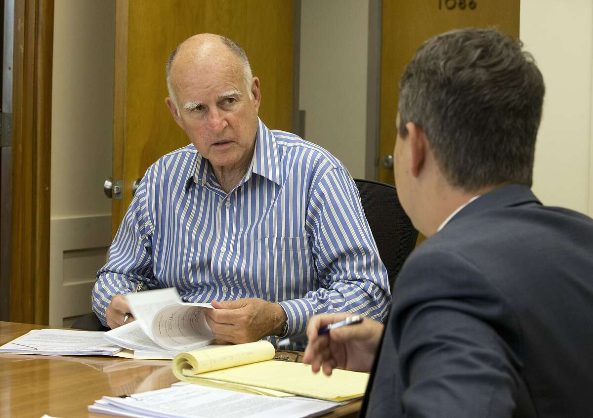 Gov. Jerry Brown, left, discusses a bill under consideration for his signature with Daniel Seeman, his deputy legislative affairs secretary Thursday, June 30, 2016, in Sacramento, Calif. Brown spent his day reviewing some of the dozens of pieces of legislation approved by lawmakers before they left for a one month summer vacation. The governor is expected to act on several gun control measures approved by lawmakers in the next few days. (AP Photo/Rich Pedroncelli)