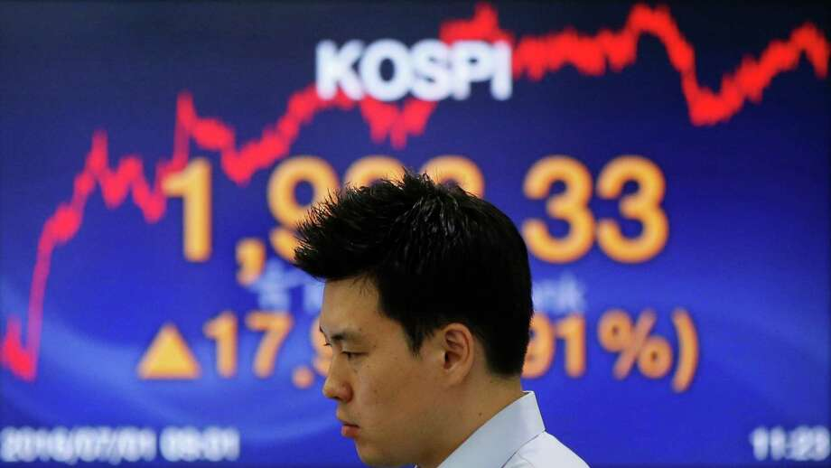 A currency trader looks at the monitors near a screen showing the Korea Composite Stock Price Index at the foreign exchange dealing room in Seoul, South Korea, on Friday. Asian shares mostly rose Friday with investors remaining in a buying mood. Photo: Lee Jin-man, STF / Copyright 2016 The Associated Press. All rights reserved. This material may not be published, broadcast, rewritten or redistribu