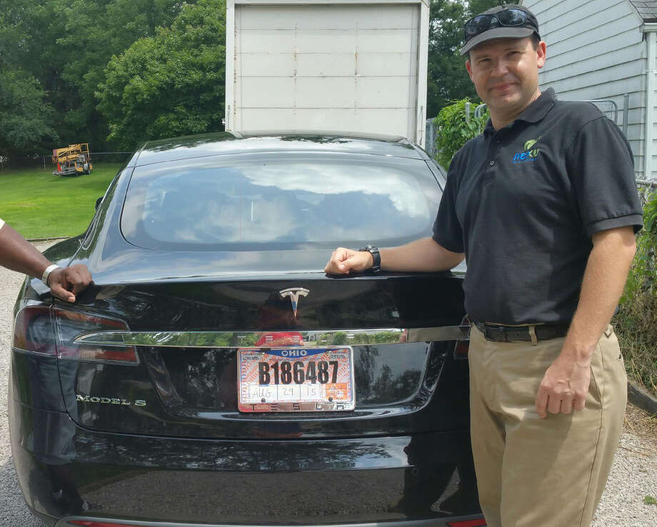 In this 2015 photo provided by his neighbor, Krista Kitchen, Joshua Brown stands by his new Tesla electric car near his home in Canton, Ohio. Brown died in an accident in Florida on May 7, 2016 in the first fatality from a car using self-driving technology. According to statements by the government and the automaker, his vehicle's cameras didn't make a distinction between the white side of a turning tractor-trailer and the brightly lit sky while failing to automatically activate its brakes. (Krista Kitchen via AP) Photo: Krista Kitchen, HONS / Krista Kitchen