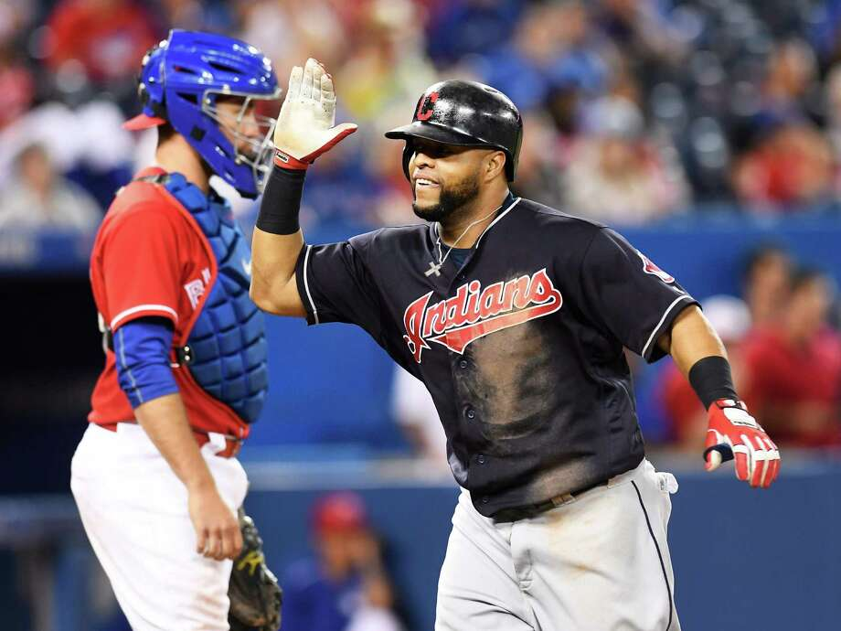 Cleveland Indians' Carlos Santana, right, celebrates his home run in front of Toronto Blue Jays catcher Josh Thole during the 19th inning of a baseball game in Toronto on Friday, July 1, 2016.  The Indians won 2-1 in 19 innings. (Frank Gunn/The Canadian Press via AP) ORG XMIT: FNG537 Photo: Frank Gunn / CP