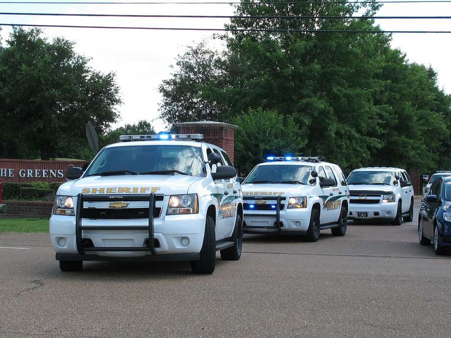 Sheriff's vehicles leave a gated neighborhood in sub urban Memphis where four children were slain. Photo: Adrian Sainz, Associated Press