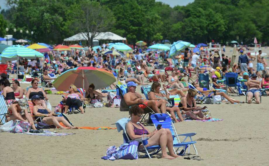 Beach goers flock to Calf Pasture Beach in Norwalk, Conn. Saturday, July 2, 2016, to celebrate the Independence Day weekend. Extra entrance attendants and non-residents parking at nearby Taylor Farm is part of Norwalk's plan to deal with expected record-breaking crowds at the beach over the 2016 Fourth of July weekend. Residents planning to attend Sunday evening fireworks are advised to arrive during the day to get a parking space. Photo: Erik Trautmann, Hearst Connecticut Media / (C)2016, Norwalk Hour, all rights reserved
