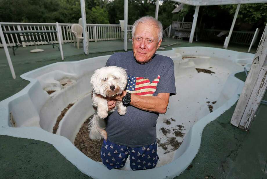 John Shull, standing in his empty 20,000-gallon pool while holding his dog, is battling San Antonio Water System over a water bill of nearly $1,700 for more than 157,000 gallons of water in a month. Shull said he didn't use that much water, and leaks could not be the cause of the extraordinary amount recorded on his bill. SAWS has given him a credit for part but has threatened to turn off his water if he doesn't pay the remainder. For context, Shull would have had to fill and empty his pool nearly eight times in a month to equal the amount recorded on the bill. Photo: Kin Man Hui /San Antonio Express-News / ©2016 San Antonio Express-News