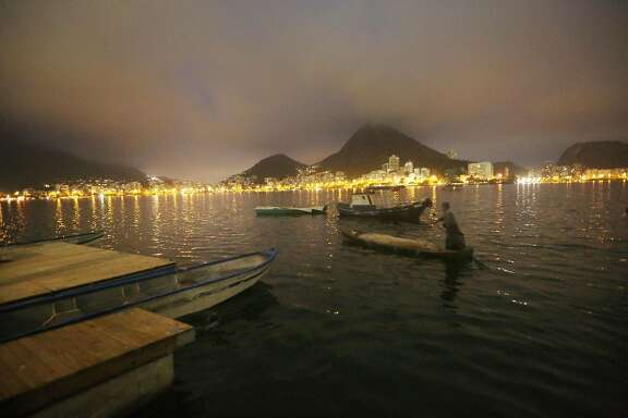 "RIO DE JANEIRO, BRAZIL - JULY 01:  A fisherman paddles in the polluted Rodrigo de Freitas Lagoon, venue for the rowing events at the Rio 2016 Olympic Games, on July 1, 2016 in Rio de Janeiro, Brazil. The U.S. Olympic Rowing Team announced the team will wear unisuits with an ""antimicrobial finish"" to combat against pollution at the venue. Rio's polluted waterways have become one of many concerns surrounding the city ahead of the August 5 opening of the games. (Photo by Mario Tama/Getty Images)"