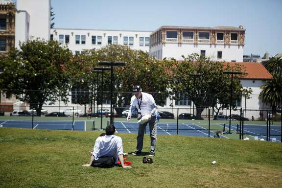 David Brenlinger of San Francisco speaks with park goers in hopes to get signatures on Saturday, July 2, 2016 at Mission Dolores Park in San Francisco, California. This ballot measure is looking to protect the San Francisco Tennis Club, which is slated to be replaced by office buildings, a smaller recreation facility, and some affordable housing.