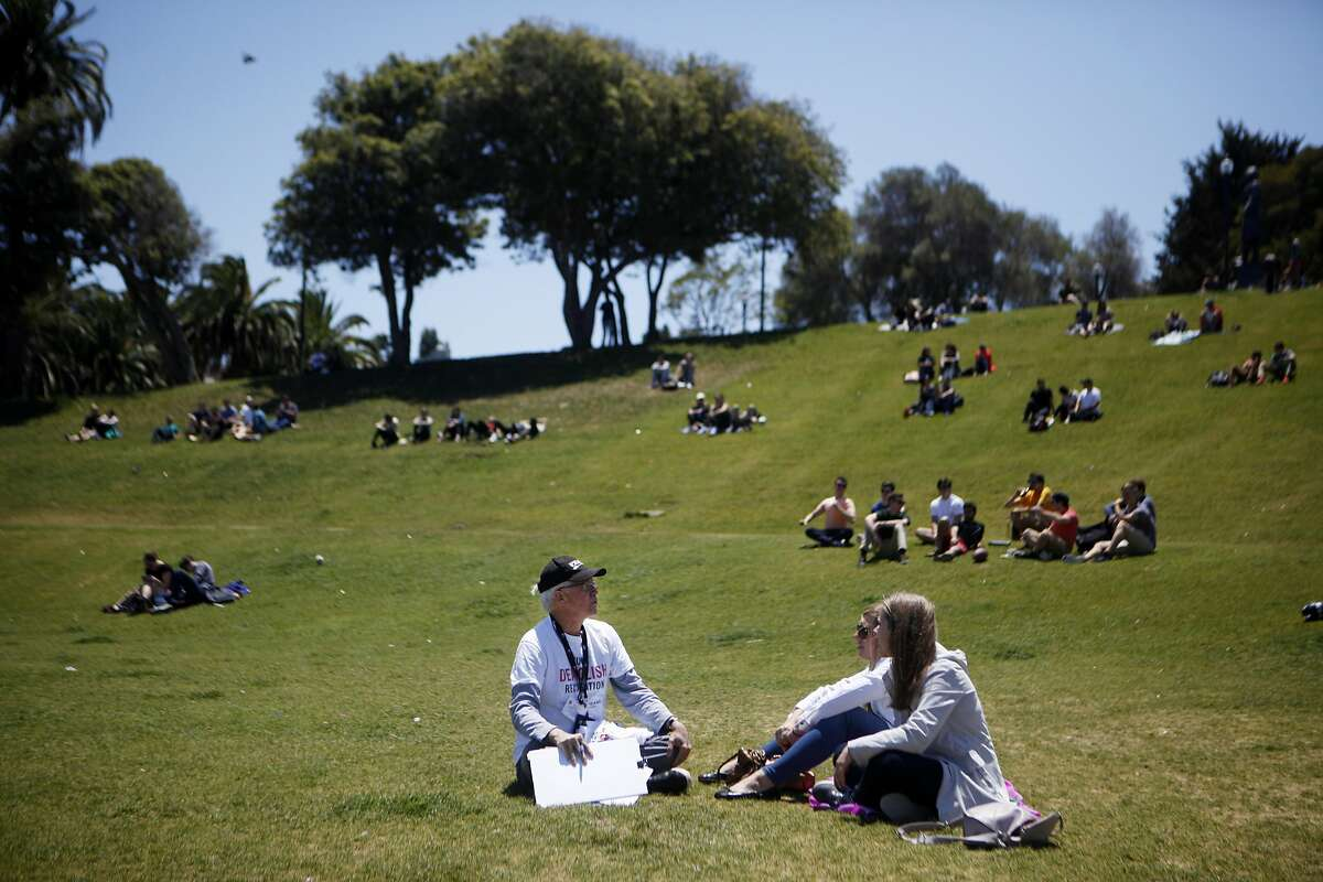 David Brenlinger of San Francisco speaks with Rebecca Patterson and Claire Shanley in hopes to get signatures on Saturday, July 2, 2016 at Mission Dolores Park in San Francisco, California. This ballot measure is looking to protect the San Francisco Tennis Club, which is slated to be replaced by office buildings, a smaller recreation facility, and some affordable housing.