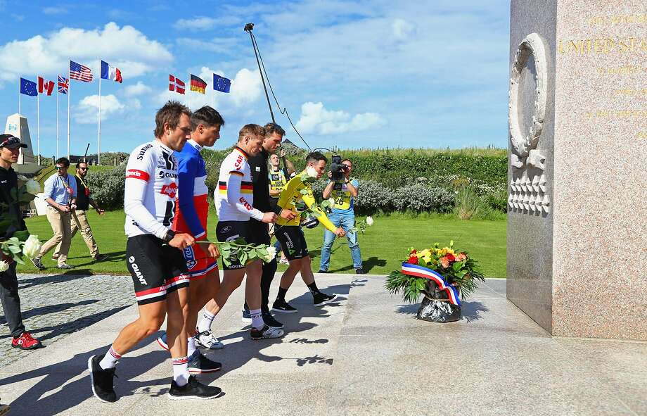 Stage winner Mark Cavendish (yellow jersey) and fellow riders place flowers at a war memorial at Utah Beach honoring the soldiers who died on D-Day — June 6, 1944. Photo: Michael Steele, Getty Images