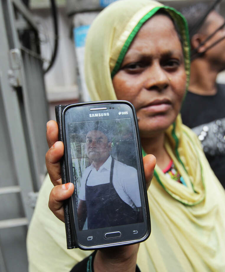 Johura Begum shows a photograph of her brother-in-law Saidul Islam, who works at the Holey Artisan Bakery and currently missing, at the site of an attack by heavily armed militants, in Dhaka, Bangladesh, Saturday, July 2, 2016. The dramatic, 10-hour hostage crisis that gripped the Bangladesh's diplomatic zone ended Saturday morning as commandos raided the popular restaurant where dozens of foreigners and Bangladeshis were dining out during the Ramadan holy month. (AP Photo) ORG XMIT: DEL157 / Copyright 2016 The Associated Press. All rights reserved. This m