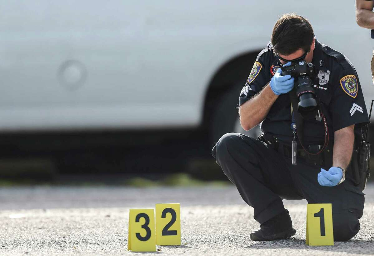A Houston Police Department officer photographs a bullet casing during an investigation of a homicide at an apartment complex on Wednesday, June 15, 2016, in Houston. ( Elizabeth Conley / Houston Chronicle )