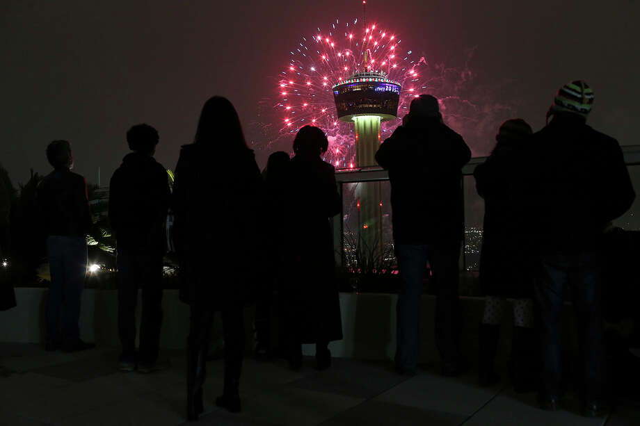 Residents and guest of the Alteza Residences watch Celebrate San Antonio  New Year fireworks display by the Tower of the Americas, Thursday, Jan. 1, 2015. A crowd of 70,000 was expected to attend the event that is considered the largest free New Year's celebration in Texas. Photo: JERRY LARA, Staff / San Antonio Express-News / © 2014 San Antonio Express-News