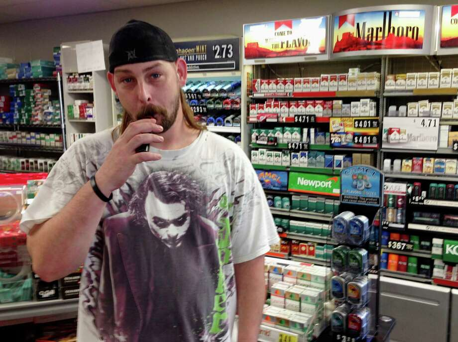 In this June 23, 2016 photo, Kenneth Houser takes a puff on an electronic cigarette at the We B Smokin store where he works in Jefferson City, Mo. Houser says he has smoked traditional cigarettes since age 13 but is trying to quit, partly because of the potential for prices to rise under a pair of tobacco tax initiatives proposed for the Missouri ballot. (AP Photo/David A. Lieb) Photo: David A. Lieb, STF / Copyright 2016 The Associated Press. All rights reserved. This material may not be published, broadcast, rewritten or redistribu