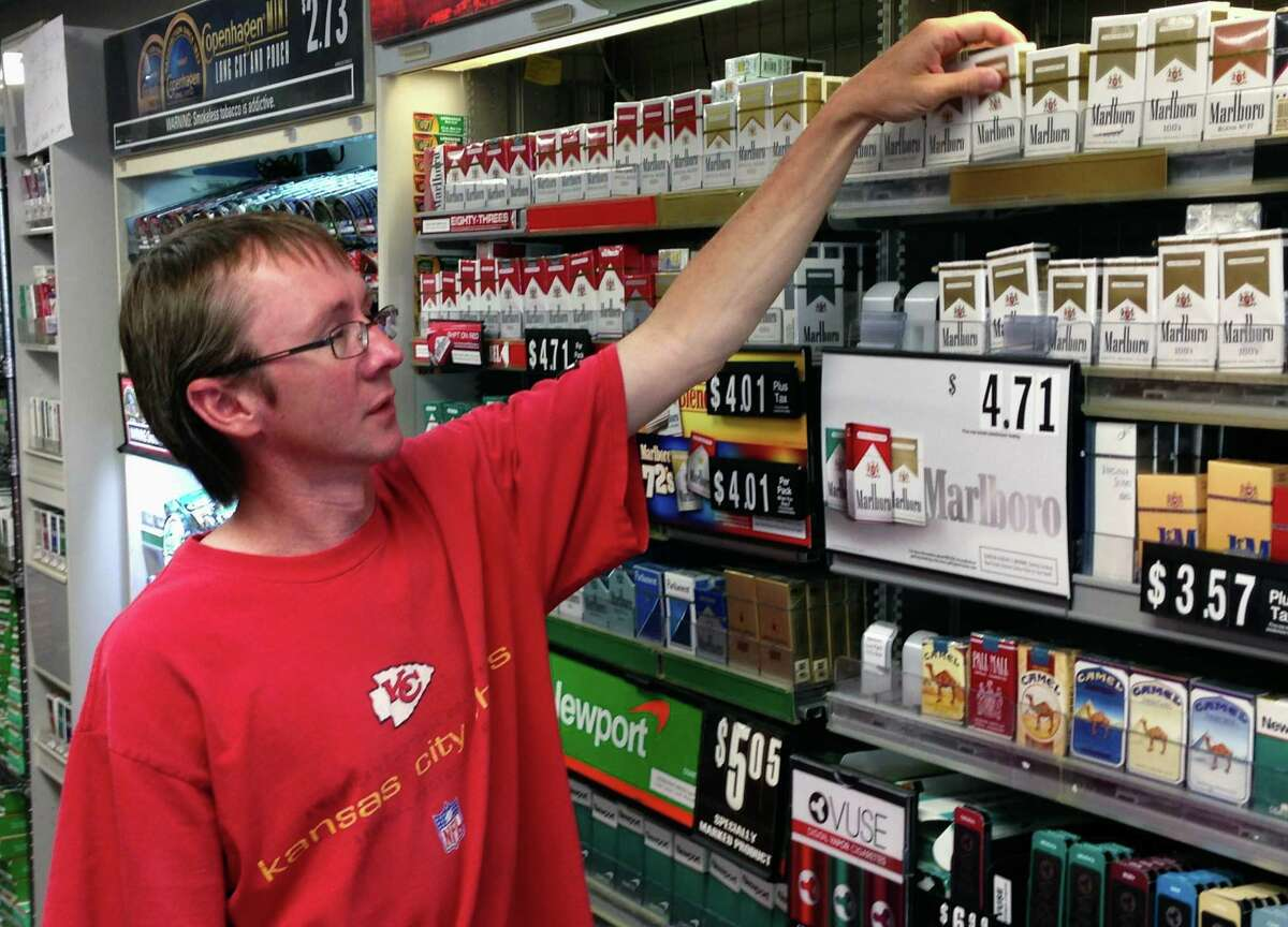 Charlie Hake, owner of We B Smokin in Jefferson City, Mo., reaches for a pack of cigarettes at his store. Hake opposes to raise the state's cigarette tax.