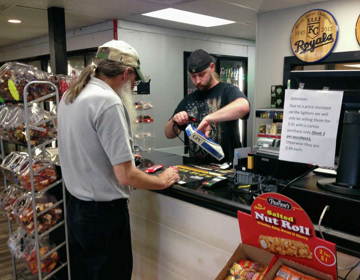 In this June 23, 2016 photo, Kenneth Houser sells a carton of cigarettes to a customer at the We B Smokin store in Jefferson City, Mo. A pair of proposed ballot initiatives seek to raise Missouri's lowest-in-the-nation cigarette tax. (AP Photo/David A. Lieb)