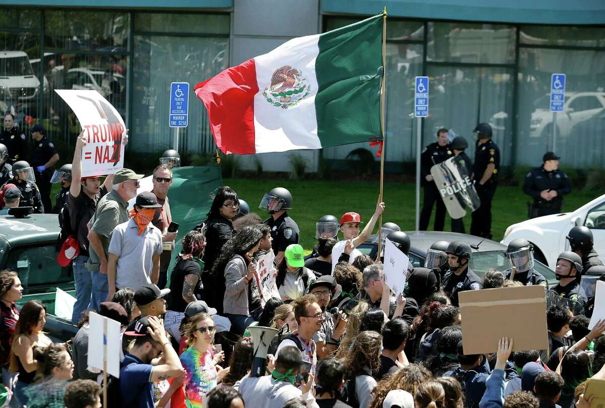 File - In this April 29, 2016, file photo, a protester against Republican presidential candidate Donald Trump waves a flag of Mexico outside of the Hyatt Regency hotel where the California Republican Party 2016 Convention is taking place in Burlingame, Calif., Friday, April 29, 2016. It's a flag seen at many protests against presumptive Republican presidential nominee Donald Trump. It also can be spotted at immigration rallies, on murals in cities with sizable Latino populations and at Mexican National team soccer games held on U.S. soil. The flag of Mexico has a long history in the United States, despite being a symbol of a nation south of the border. (AP Photo/Eric Risberg, File)