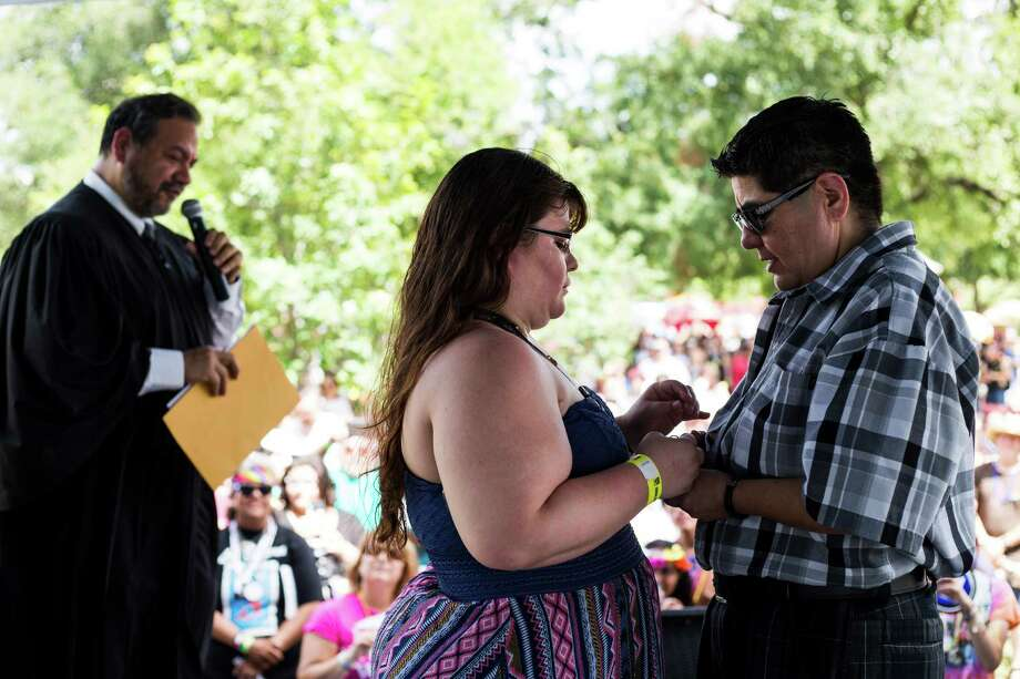 """Ashley Hartman, 28, and Veronica Martinez, 29, exchange wedding rings as they take their vows before a small crowd during the 13th annual """"Bigger Than Texas"""" Pride Festival at Crockett Park in San Antonio on Saturday, July 2, 2016. Photo: BRITTANY GREESON, Staff / San Antonio Express-News / © 2015 San Antonio Express-News"""