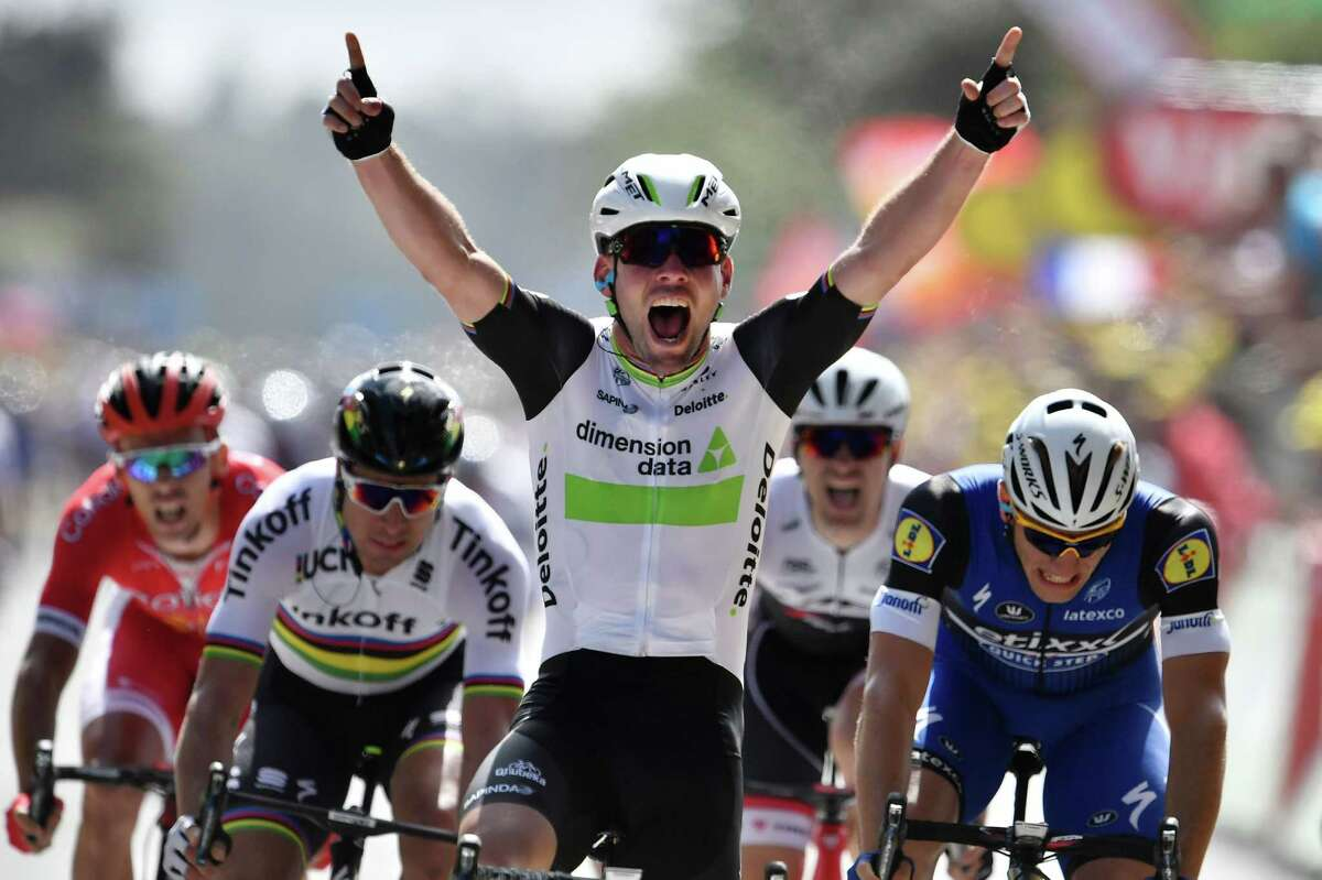 Great Britain's Mark Cavendish celebrates as he crosses the finish line ahead of Germany's Marcel Kittel (R) and Slovakia's Peter Sagan (2ndL) at the end of the 188 km first stage of the 103rd edition of the Tour de France cycling race on July 2, 2016 between Mont-Saint-Michel and Utah Beach Sainte-Marie-du-Mont, Normandy. / AFP PHOTO / jeff pachoudJEFF PACHOUD/AFP/Getty Images
