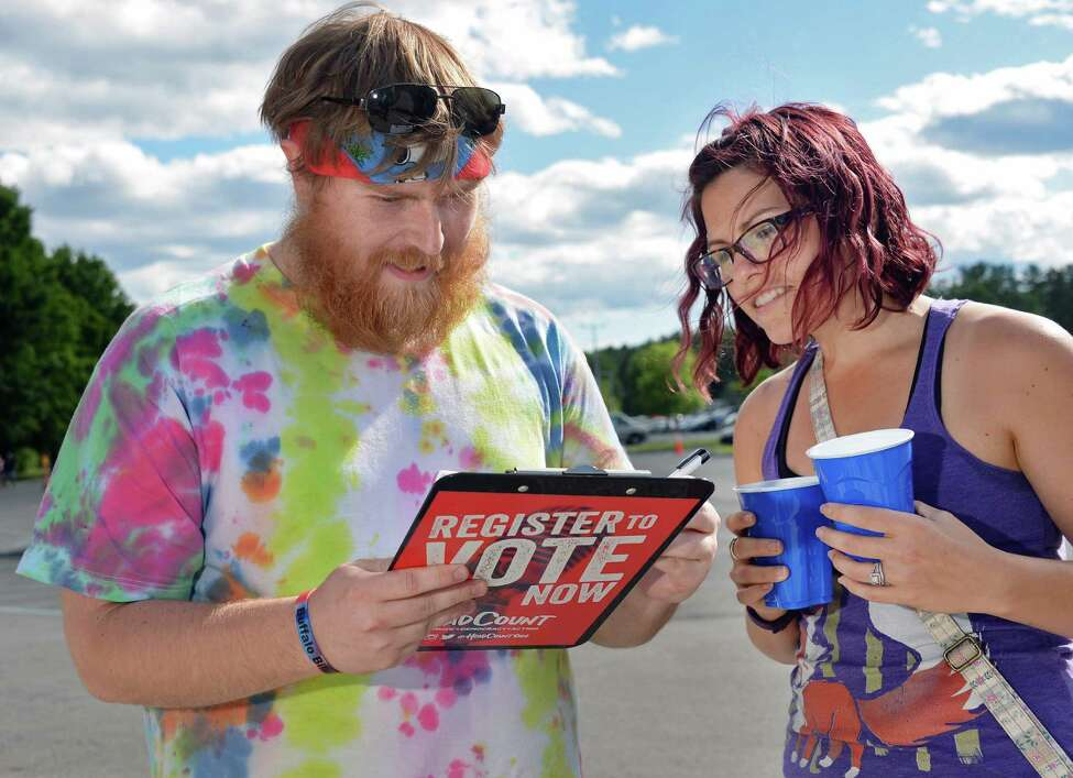 Brandon Hika, left, of Middlegrove registers to vote as his sister Ashlee Schmidt of Albany looks on at the Headcount booth outside SPAC before the Phish concert Saturday July 2, 2016 in Saratoga Springs, NY. (John Carl D'Annibale / Times Union)