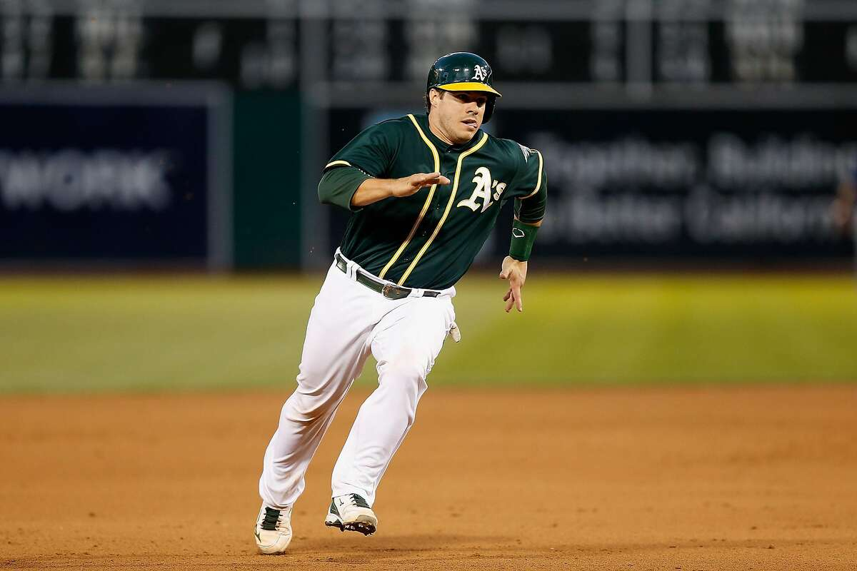 OAKLAND, CA - JUNE 15: Josh Phegley #19 of the Oakland Athletics runs to third base and on to score on a double hit by Billy Burns #1 of the Oakland Athletics in the fourth inning against the Texas Rangers at O.co Coliseum on June 15, 2016 in San Francisco, California. (Photo by Lachlan Cunningham/Getty Images)