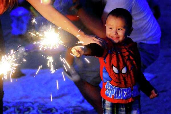 Dylan Daza, 3, of Stamford, plays with a sparkler during the Independence Day celebration at Cummings Park in Stamford, Conn., on Saturday July 2, 2016.