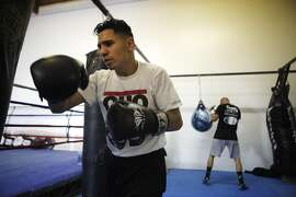 """Manuel """"Tino"""" Avila and Ryan """"Rhino"""" Borland work the bags  during a training session on Friday, July 1, 2016 in Benicia, California."""