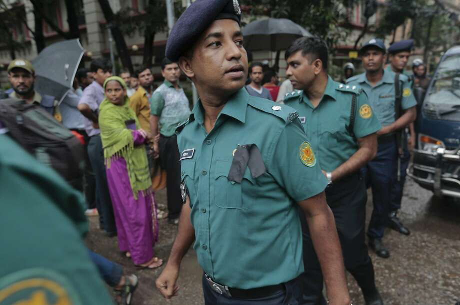 Police officers in Dhaka wear black badges on the first of two days of national mourning for the victims. Photo: Associated Press
