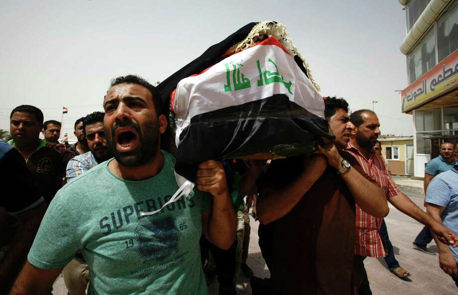 Iraqi men carry a coffin in the holy Iraqi city of Najaf on July 3, 2016, during a funeral procession for the victims of a suicide bombing that ripped through Baghdad's busy shopping district of Karrada. The blast hit the Karrada district early in the day as the area was packed with shoppers ahead of this week's holiday marking the end of the Muslim fasting month of Ramadan, killing at least 75 people in the deadliest single attack this year in Iraq's capital.     / AFP PHOTO / Haidar HAMDANIHAIDAR HAMDANI/AFP/Getty Images Photo: HAIDAR HAMDANI / AFP or licensors