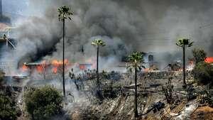 Several hilltop homes burn on Skylark Dr. in San Bernardino following a fast-moving brush fire, on Saturday, July 2, 2016. (David Bauman/The Press-Enterprise via AP)
