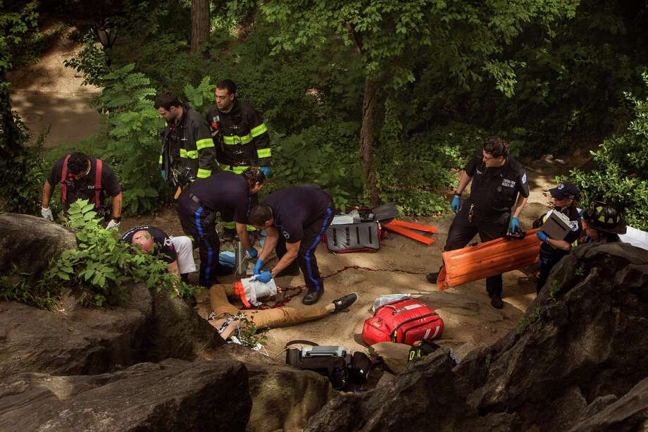 A man, center bottom, bleeds from his injured leg as he gets helped from paramedics, firemen, and police in Central Park in New York, Sunday, July 3, 2016. Police and emergency responders took the man on a stretcher from New York's Central Park after people near the area reported hearing some kind of explosion. Fire officials say it happened shortly before 11 a.m., inside the park at 68th Street and Fifth Avenue. Authorities say the man suffered serious injuries and was taken to the hospital. (AP Photo/Andres Kudacki) ORG XMIT: NYAK103 Photo: Andres Kudacki / FR170905 AP