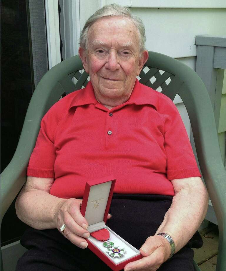 In this June 29, 2016 photo, James Facos holds a medal in Montpelier, Vt., that he received as part of his induction into the French Legion of Honor for his service defending that country in World War II. The French have been bestowing their highest honor on U.S. veterans who were distinguished in their efforts to defeat the Nazis. Facos flew 30 missions with the Eighth Air Force over France in Germany in 1944 as a ball turret gunner on a B-17 bomber. (AP Photo/Dave Gram) Photo: Dave Gram, STF / Copyright 2016 The Associated Press. All rights reserved. This material may not be published, broadcast, rewritten or redistribu