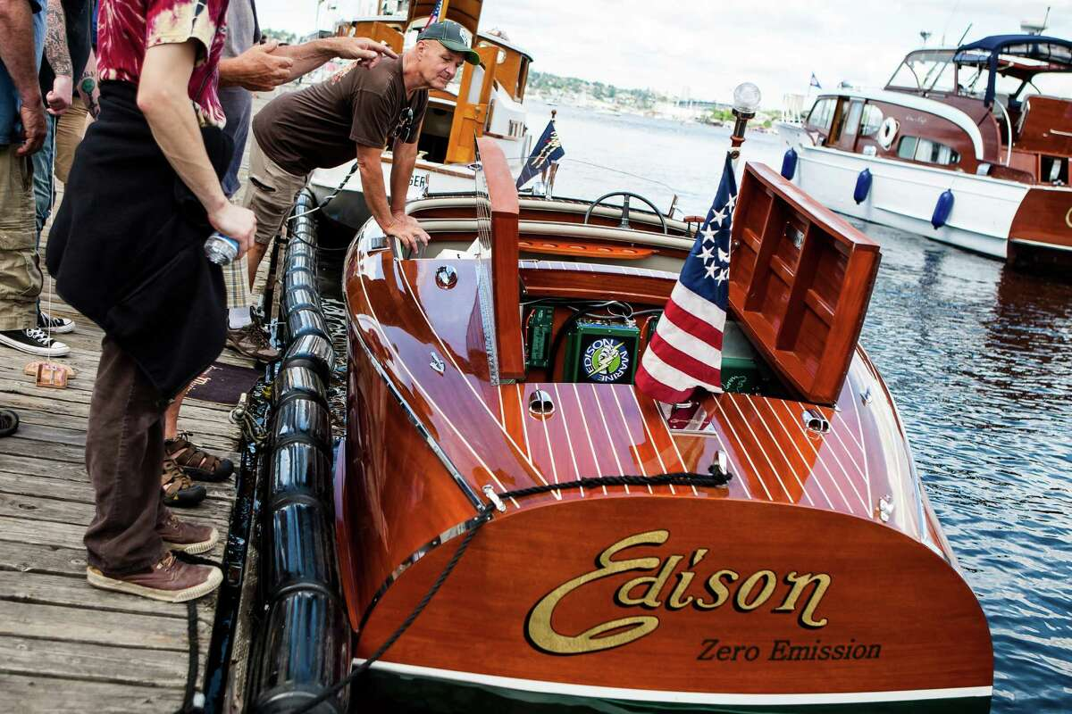 A festival goer takes a look inside the engine compartment of the Edison - a wooden boat on display during the Lake Union Wooden Boat Festival on July 2, 2016. Each boat on display had a designated ballot box so festival goers could vote for their favorite wooden boat at the festival.