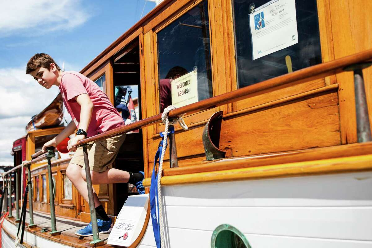 A young festival goer climbs out of the cabin of Seven Bells after taking a tour of the vessel during the Lake Union Wooden Boat Festival on July 2, 2016.