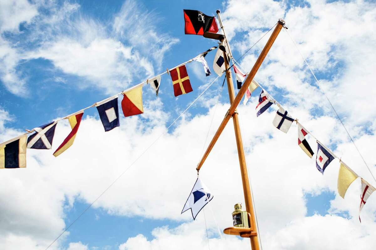 A line of flags hangs from the mast of a wooden boat during the Lake Union Wooden Boat Festival on July 2, 2016.