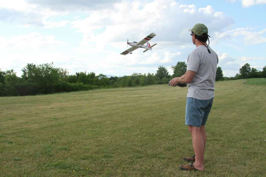 A remote-controlled aircraft swoops past its pilot Bob Lippman, a Saratoga Springs lawyer and president of the North Country Flying Tigers Model Airplane Club. The club will hold their annual Fun Fly Charity Airshow July 9, which will raise money for the American Legion. (Photo: J.p. Lawrence).