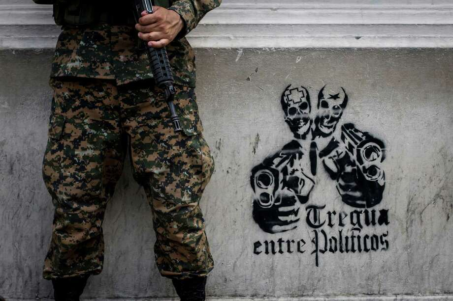 "A soldier stands next to stenciled graffiti that reads in Spanish ""Truce between politicians"" painted on a wall of the National Palace in San Salvador. Photo: Salvador Melendez, STR / AP"