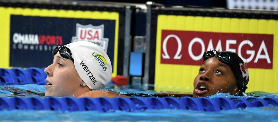 Abbey Weitzeil, left, and Simone Manuel check their times after the women's 50-meter freestyle at the U.S. Olympic swimming trials Sunday. Photo: Mark J. Terrill, STF / Copyright 2016 The Associated Press. All rights reserved. This material may not be published, broadcast, rewritten or redistribu
