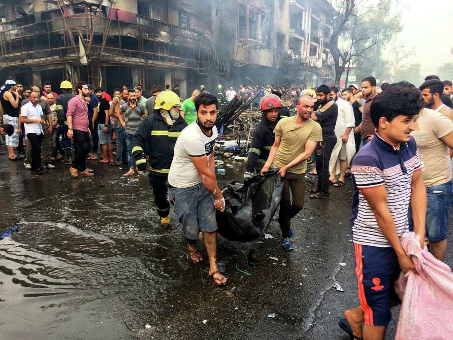 Iraqi firefighters and civilians carry bodies of victims killed in a car bomb at a commercial area in Karada neighborhood, Baghdad, Iraq, Sunday, July 3, 2016. Bombs went off early Sunday in two crowded commercial areas in Baghdad. (AP Photo/Khalid Mohammed) ORG XMIT: BKM103 Photo: Khalid Mohammed / Copyright 2016 The Associated Press. All rights reserved. This m