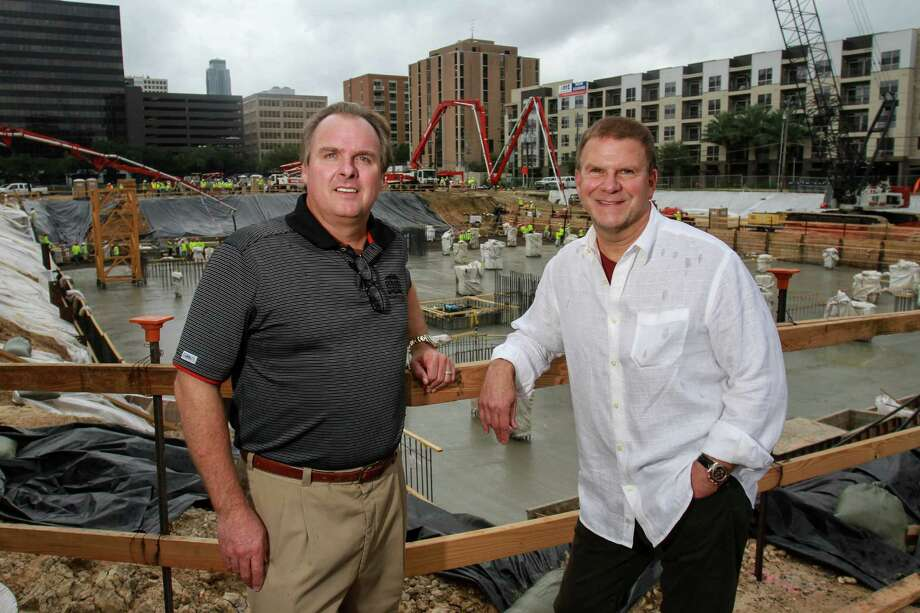 "Landry's senior VP of development Jeff Cantwell, left, and CEO Tilman Fertitta during the concrete pour for The Post Oak, Houstoné¢Ã©""é´s first vertical mixed-use, master-planned project, a 35-story tower that combines hotel, office, residential, retail and restaurant offerings for the development. 700 trucks delivering approximately 6,000 cubic yards of concrete to the site continuously, with as many as 70 trucks on-site at the same time. Six concrete pump trucks and 200 workers pumping cement at a rate of 600 cubic yards per hour. Concrete pour encases 1,000 tons of rebar already in place in a 23-foot deep and 35,000 square foot hole.(For the Chronicle/Gary Fountain, October 30, 2015) Photo: Gary Fountain, For The Chronicle / Copyright 2015 Gary Fountain"
