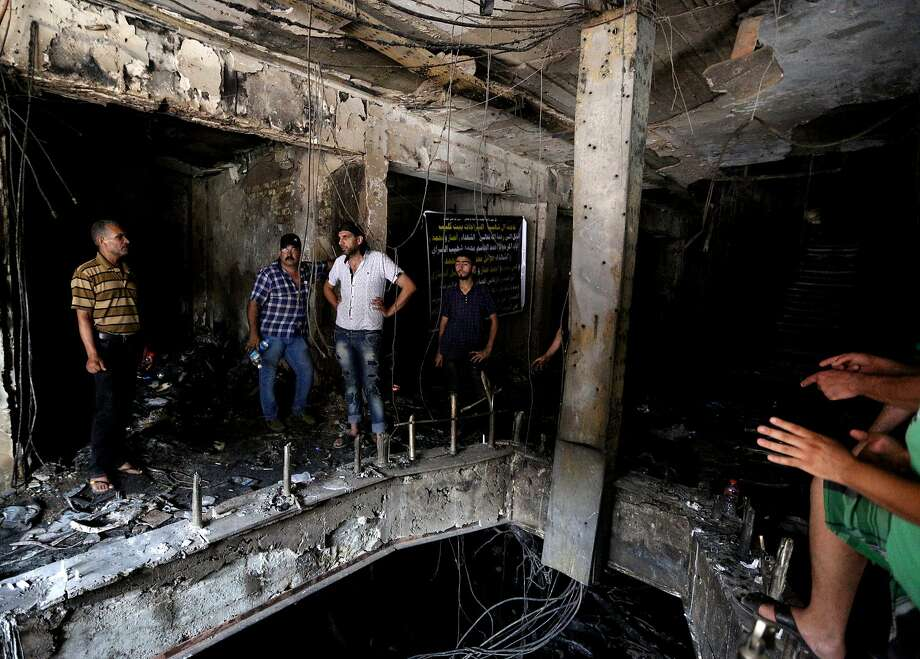 Iraqi men look for victims who went missing after a car bomb hit Karada, a busy shopping district in the center of Baghdad, Iraq, Monday, July 4, 2016. More than 100 people died Sunday in a car bombing that Islamic State said it carried out, an official of the Iraqi Interior Ministry said. (AP Photo/Hadi Mizban) Photo: Hadi Mizban, Associated Press