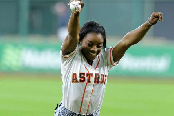 Simone Biles, of Spring, who will participate in the upcoming Olympic Games in Rio, performs a side aerial as she throws out a ceremonial first pitch before the Houston Astros and Seattle Mariners game at Minute Maid Park Monday, July 4, 2016, in Houston.