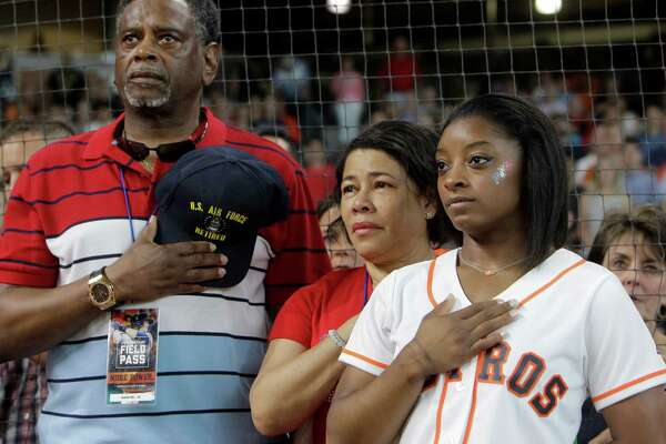 Ron Biles and Nellie Biles with their daughter, Simone Biles, of Spring, who will participate in the upcoming Olympic Games in Rio, during the National Anthem before at the Houston Astros and Seattle Mariners game at Minute Maid Park Monday, July 4, 2016, in Houston. She throw out a ceremonial first pitch before the game.
