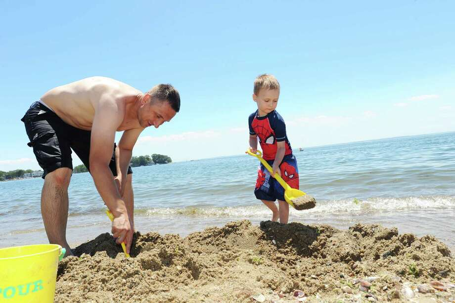 Four-year old Matthew Yasniy and his father Volodymyr dig a sand castle at Cove Island Beach on Monday, July 4, 2016. Photo: Michael Cummo / Hearst Connecticut Media / Stamford Advocate
