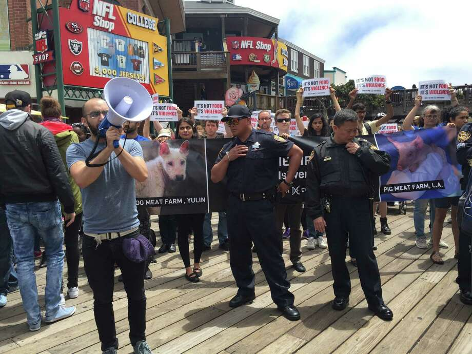 Samer Masterson, 22, leads group chants inside Pier 39 as security guards try to quell the disruption. Photo: Kimberly Veklerov / The Chronicle