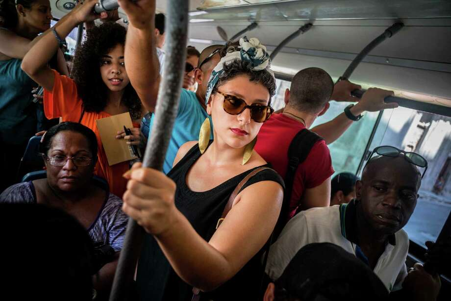 In this June 12, 2016 photo, Cuban American Fontaine Capel, center, travels on a regular bus line in Havana, Cuba. Capel was brought to the island by CubaOne, a new program inspired by the reestablishment of diplomatic and business ties between the U.S. and Cuba. (AP Photo/Ramon Espinosa) ORG XMIT: XRE103 Photo: Ramon Espinosa / Copyright 2016 The Associated Press. All rights reserved. This m